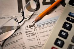 Tax forms with calculator and glasses