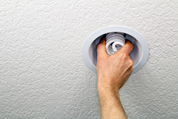 screwing in energy efficient light bulb