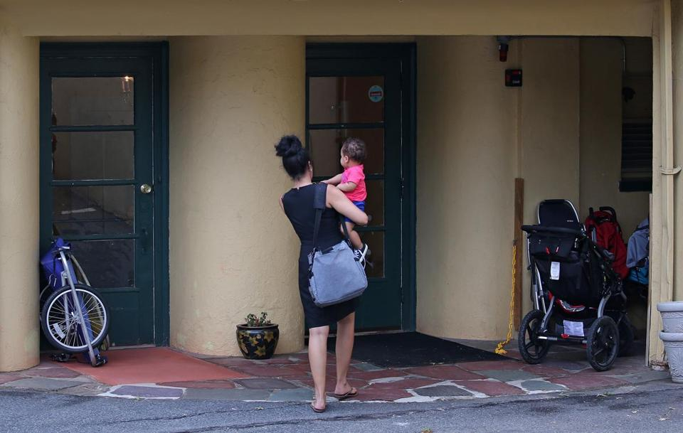 A mother carries her child into an early education and daycare center