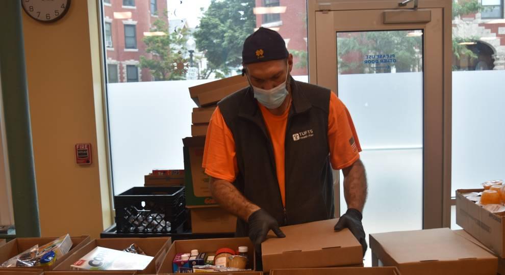 Volunteer Mark Mackin packs boxes of food at an ABCD food bank in Roxbury. Craig LeMoult / WGBH News
